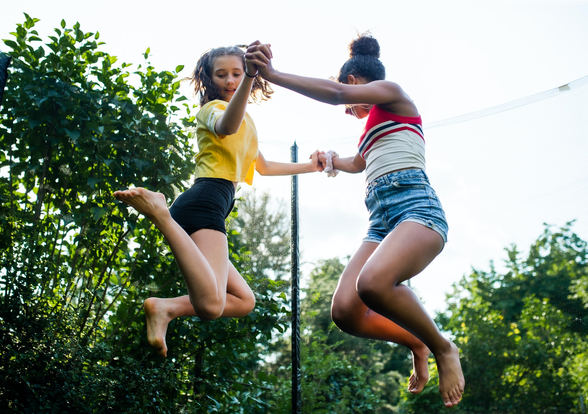Low angle view of young teenager girls friends outdoors in garden, jumping on trampoline