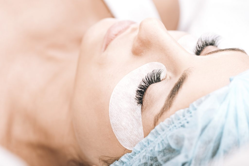 model with false eyelashes and closed eyes lying on couch after eyelash extensions